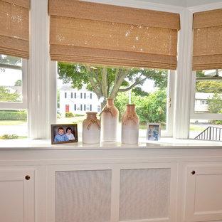 Modelo de sala de estar abierta, clásica renovada, pequeña, con paredes grises, suelo de madera en tonos medios, chimenea tradicional, marco de chimenea de piedra y televisor colgado en la pared