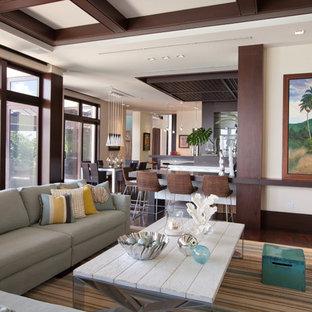 マイアミの中サイズのトロピカルスタイルのおしゃれなファミリールーム (ベージュの壁、カーペット敷き、暖炉なし、グレーの床) の写真