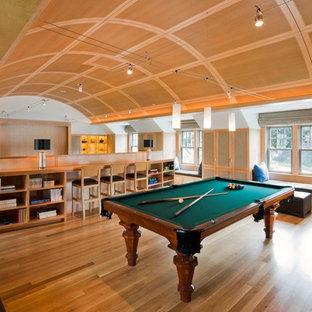 Immagine di un ampio soggiorno chic aperto con sala giochi, pareti grigie, parquet chiaro, nessun camino e pavimento marrone