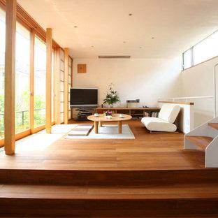 Esempio di un grande soggiorno design aperto con pareti bianche, pavimento in legno massello medio, nessun camino e porta TV ad angolo