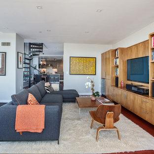 ニューヨークのコンテンポラリースタイルのおしゃれな独立型ファミリールーム (白い壁、濃色無垢フローリング、壁掛け型テレビ、赤い床) の写真