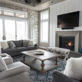 Cette image montre une grande salle de séjour marine fermée avec un mur gris, un téléviseur fixé au mur, un sol en bois foncé, une cheminée standard, un manteau de cheminée en béton et un sol marron.
