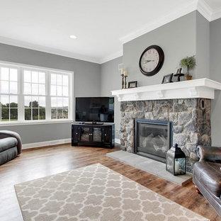 Immagine di un grande soggiorno classico aperto con pareti grigie, pavimento in vinile, camino classico, cornice del camino in pietra, porta TV ad angolo e pavimento marrone