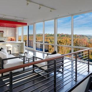 Ejemplo de sala de estar abierta, contemporánea, pequeña, sin televisor y chimenea, con suelo de cemento, paredes blancas y suelo negro