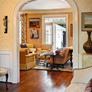 Example of a mid-sized classic open concept light wood floor family room design in Raleigh with beige walls and no fireplace