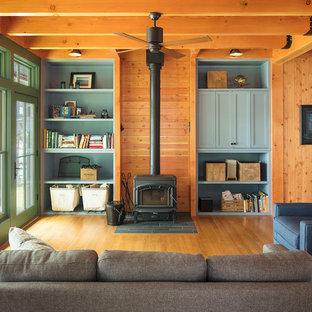Ispirazione per un soggiorno stile rurale aperto con pavimento in legno massello medio, stufa a legna e TV nascosta