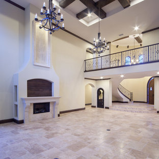 Foto di un ampio soggiorno mediterraneo aperto con pareti bianche, pavimento in travertino, camino classico, cornice del camino in metallo e TV a parete