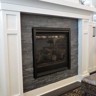 Ejemplo de sala de estar abierta, ecléctica, pequeña, con paredes grises, suelo de madera oscura, chimenea tradicional, marco de chimenea de piedra, televisor colgado en la pared y suelo marrón