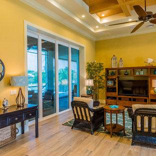 マイアミの大きいビーチスタイルのおしゃれなオープンリビング (黄色い壁、セラミックタイルの床、埋込式メディアウォール) の写真