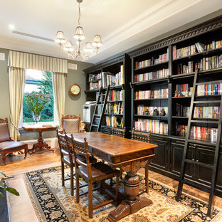 Mid-sized traditional enclosed family room in Melbourne with a library, grey walls, medium hardwood floors, a standard fireplace and brown floor.