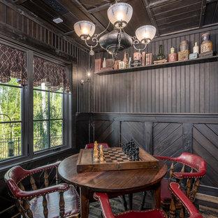 Diseño de sala de juegos en casa de estilo de casa de campo, grande, con paredes negras, suelo de madera oscura y suelo marrón