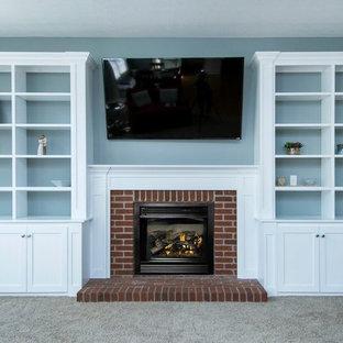 Foto di un soggiorno tradizionale di medie dimensioni e chiuso con pareti blu, moquette, camino classico, cornice del camino in mattoni, TV a parete e pavimento grigio