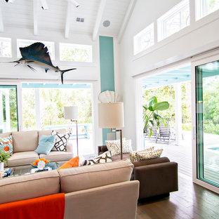 ジャクソンビルの大きいトロピカルスタイルのおしゃれなファミリールーム (青い壁、無垢フローリング、壁掛け型テレビ) の写真
