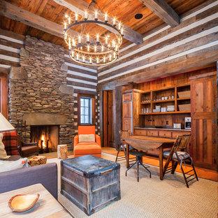 Modelo de sala de juegos en casa cerrada, rural, con paredes marrones, suelo de madera en tonos medios, chimenea tradicional, marco de chimenea de piedra y suelo naranja
