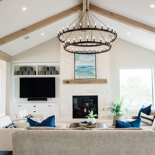 Inspiration for a large transitional open concept light wood floor and beige floor family room remodel in Austin with a standard fireplace, a stone fireplace, a wall-mounted tv and beige walls