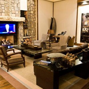 デンバーの巨大なラスティックスタイルのおしゃれなオープンリビング (マルチカラーの壁、標準型暖炉、石材の暖炉まわり、内蔵型テレビ、無垢フローリング、茶色い床) の写真