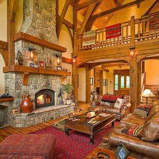 Aménagement d'une grand salle de séjour montagne ouverte avec un sol en bois brun, une cheminée ribbon, un manteau de cheminée en pierre et un mur blanc.