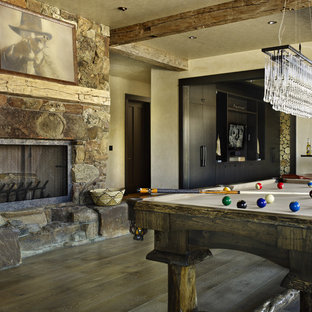 Mountain style game room photo in Denver with beige walls, a standard fireplace and a stone fireplace