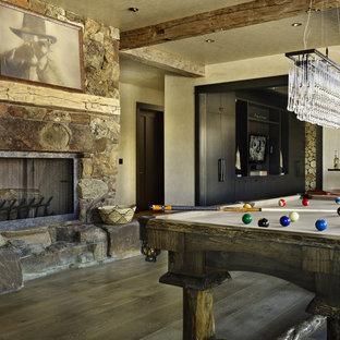 Immagine di un soggiorno stile rurale con sala giochi, pareti beige, camino classico e cornice del camino in pietra