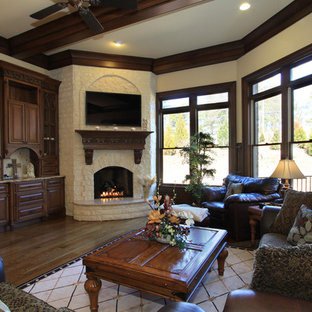 Huge elegant open concept medium tone wood floor family room photo in Atlanta with beige walls, a corner fireplace, a stone fireplace and a wall-mounted tv
