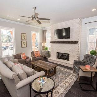 アトランタの中くらいのカントリー風おしゃれな独立型ファミリールーム (ベージュの壁、濃色無垢フローリング、標準型暖炉、レンガの暖炉まわり、壁掛け型テレビ、茶色い床) の写真