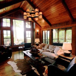 Réalisation d'une grand salle de séjour tradition ouverte avec un mur marron, un sol en bois foncé, une cheminée standard et un manteau de cheminée en pierre.