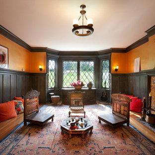 Réalisation d'une salle de séjour tradition avec un mur orange, un sol en bois brun et une cheminée standard.
