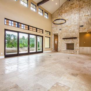 Imagen de sala de estar abierta, rural, grande, con paredes beige, suelo de travertino, chimenea tradicional, marco de chimenea de piedra y televisor colgado en la pared