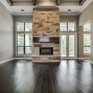 Esempio di un grande soggiorno american style chiuso con pareti beige, parquet scuro, camino classico e cornice del camino in pietra