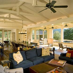 Diseño de sala de estar abierta, de estilo de casa de campo, con paredes blancas y suelo de madera oscura