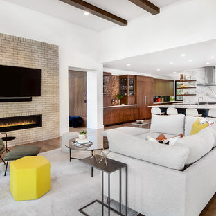 Example of a 1960s open concept medium tone wood floor family room design in Denver with white walls, a ribbon fireplace, a wall-mounted tv and a brick fireplace