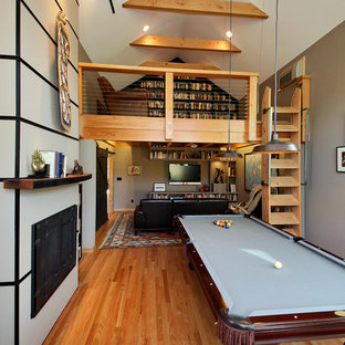 Large urban open concept medium tone wood floor game room photo in Seattle with a wall-mounted tv and multicolored walls