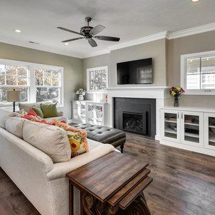 ボイシの中サイズのおしゃれなファミリールーム (グレーの壁、無垢フローリング、標準型暖炉、タイルの暖炉まわり、壁掛け型テレビ、茶色い床) の写真