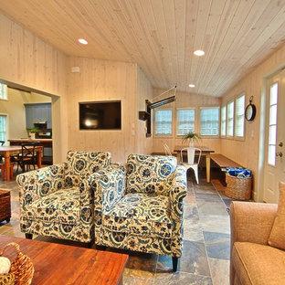 グランドラピッズの小さいビーチスタイルのおしゃれなファミリールーム (ベージュの壁、スレートの床、暖炉なし、壁掛け型テレビ) の写真