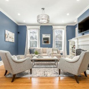 コロンバスの中くらいのトラディショナルスタイルのおしゃれな独立型ファミリールーム (青い壁、標準型暖炉、壁掛け型テレビ、無垢フローリング、ベージュの床) の写真