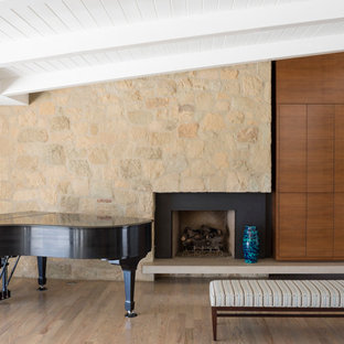 Example of a mid-sized trendy open concept medium tone wood floor and brown floor family room design in Los Angeles with a music area, white walls, a standard fireplace, a stone fireplace and a concealed tv