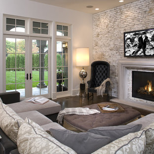 Mediterranean family room in Minneapolis with beige walls, dark hardwood floors, a standard fireplace and a wall-mounted tv.