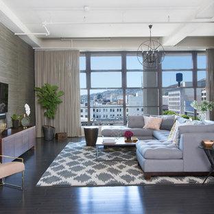 Esempio di un soggiorno industriale di medie dimensioni con pareti grigie, parquet scuro, nessun camino e TV a parete