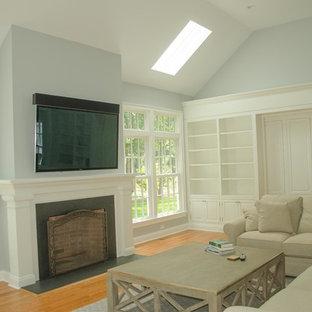 Ispirazione per un grande soggiorno classico chiuso con pareti blu, parquet chiaro, camino classico, TV a parete, cornice del camino in legno e pavimento marrone