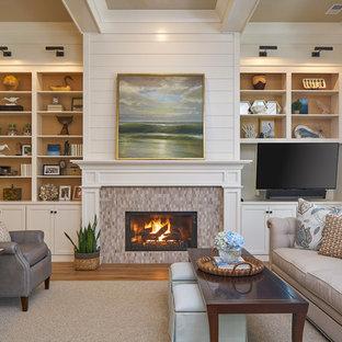 Aménagement d'une salle de séjour classique de taille moyenne et ouverte avec un mur beige, un sol en bois brun, une cheminée standard, un manteau de cheminée en carrelage et un téléviseur fixé au mur.