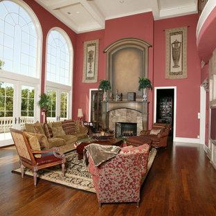 Ispirazione per un ampio soggiorno mediterraneo aperto con pareti rosse, pavimento in legno massello medio, camino classico e cornice del camino in pietra