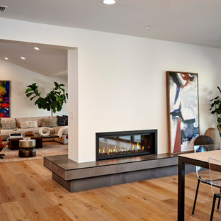 Example of a large minimalist open concept light wood floor and brown floor family room design in San Diego with white walls, a two-sided fireplace, a concrete fireplace and a wall-mounted tv