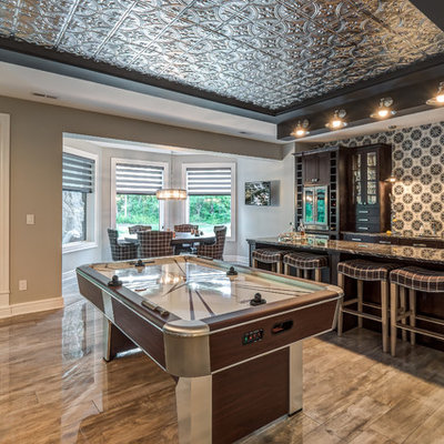 Example of a huge transitional open concept porcelain tile and brown floor family room design in Cincinnati with a bar, gray walls, no fireplace and a wall-mounted tv