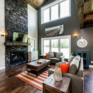 Modelo de sala de estar cerrada, campestre, grande, con paredes marrones, suelo de madera oscura, estufa de leña, marco de chimenea de piedra, televisor colgado en la pared y suelo marrón