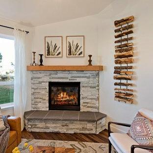 他の地域の中サイズのミッドセンチュリースタイルのおしゃれなファミリールーム (白い壁、クッションフロア、コーナー設置型暖炉、石材の暖炉まわり、壁掛け型テレビ、茶色い床) の写真