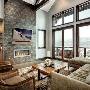 Bild på ett mellanstort rustikt allrum med öppen planlösning, med vita väggar, mellanmörkt trägolv, en bred öppen spis, en spiselkrans i trä, en väggmonterad TV, grått golv och en hemmabar