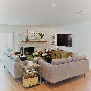 Inspiration for a mid-sized contemporary open concept light wood floor and beige floor family room remodel in Austin with white walls, a standard fireplace, a stone fireplace and a wall-mounted tv