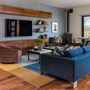 ポートランドの中サイズのラスティックスタイルのおしゃれなファミリールーム (ゲームルーム、青い壁、壁掛け型テレビ、濃色無垢フローリング、薪ストーブ、茶色い床) の写真