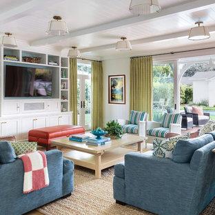 ロサンゼルスの広いビーチスタイルのおしゃれなオープンリビング (白い壁、暖炉なし、茶色い床、無垢フローリング、壁掛け型テレビ) の写真