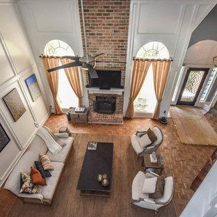 ヒューストンの広いコンテンポラリースタイルのおしゃれなオープンリビング (白い壁、無垢フローリング、標準型暖炉、レンガの暖炉まわり、壁掛け型テレビ) の写真
